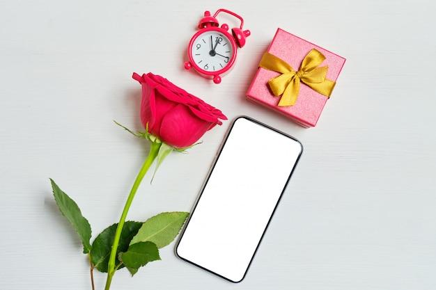 Espace de copie de téléphone avec un roses rouges, montres, boîte-cadeau