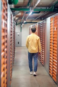 Espace d'entrepôt. vue arrière d'un homme aux cheveux noirs en chemise jaune et jeans avec la main dans sa poche marchant dans un entrepôt éclairé et propre