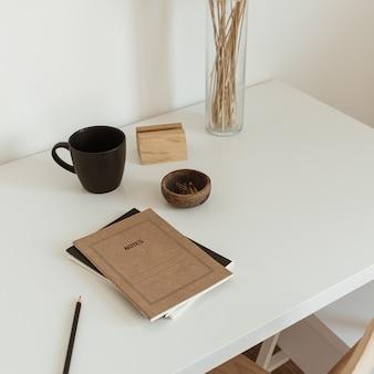 Espace hygge esthétique léger avec chaise en bois, table, bouquet d'herbe de pampa roseau, tasse, cahier