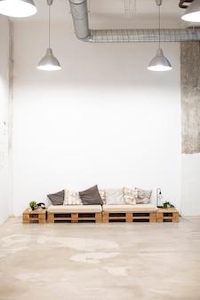 Espace industriel avec chaise et coussins en bois, plafonniers