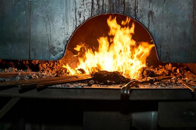 L'espace intérieur du four de forgeron avec un feu brûlant et des flans métalliques s'y réchauffant