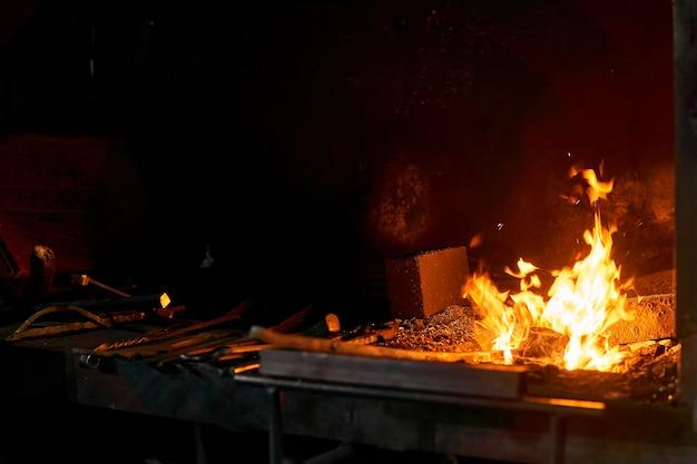 Espace intérieur du four de forgeron avec feu brûlant et outils de forge à proximité