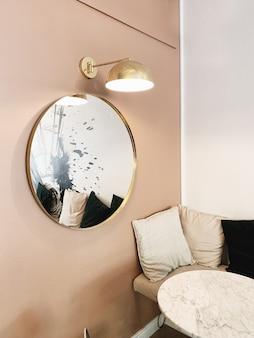 Espace ouvert lumineux avec un mur rose pâle, un miroir rond en or, une lampe en or, une table en marbre et un canapé confortable avec des rideaux moelleux