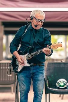 Espace photo vertical d'un vieux musicien jouant de la guitare électrique à l'extérieur