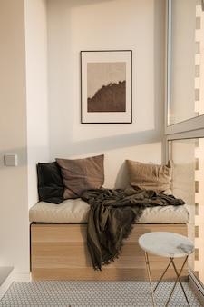 Espace salon confortable et confortable avec chaise longue loggia, mur blanc, mosaïque, table en marbre, oreillers, plaid et cadre photo