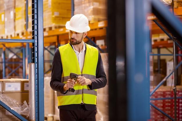 Espace de stockage. sérieux jeune homme tenant un scanner lors de la vérification de l'inventaire