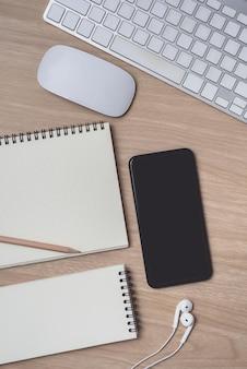 Espace de travail avec agenda ou cahier et presse-papiers, souris, ordinateur, clavier, smartphone, écouteurs, crayon, stylo