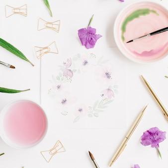Espace de travail de l'artiste. cadre de couronne florale peint à l'aquarelle, pinceaux, stylo et clips dorés, feuilles vertes