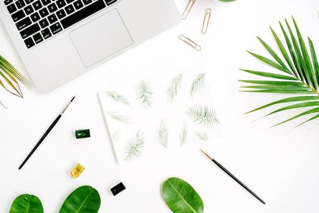 Espace de travail de l'artiste. cadre de feuilles de palmier peint à l'aquarelle, pinceaux, ordinateur portable, feuilles de palmier vert