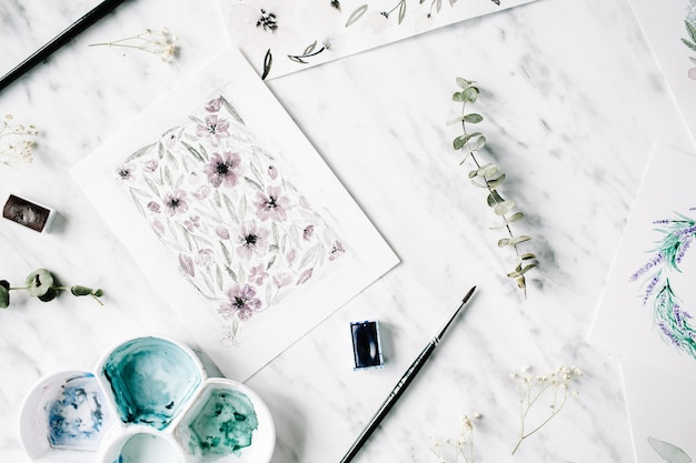 Espace de travail de l'artiste. peintures à l'aquarelle avec des cadres et des fleurs
