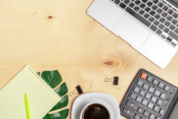 Espace de travail au bureau, bureau en bois avec ordinateur portable et vue de dessus de tasse à café