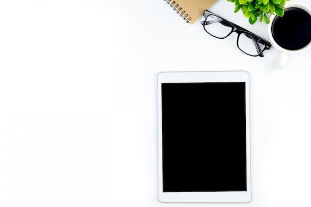 L'espace de travail au bureau avec tablette et avec des écrans vides vides est en haut, vue de dessus avec espace de copie.