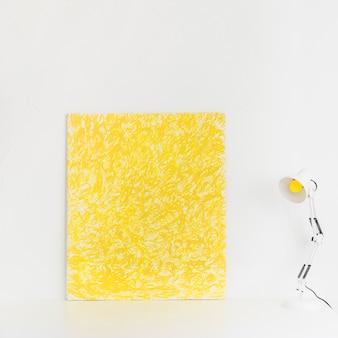 Espace de travail blanc avec photo jaune et lampe de lecture