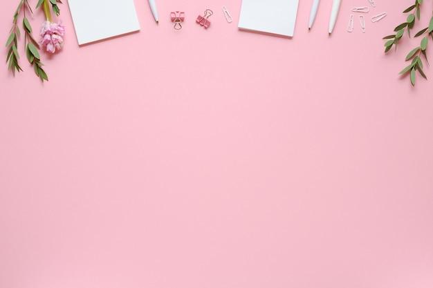 Espace de travail avec bloc-notes, stylo, trombones, eucalyptus et jacinthe sur fond rose. copiez l'espace. vue de dessus