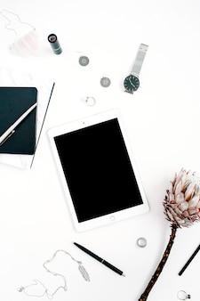 Espace de travail de blogueur ou de pigiste avec tablette à écran vierge, fleur de protéa, ordinateur portable, montres et accessoires féminins sur fond blanc. mise à plat, vue de dessus bureau à la maison décoré minimaliste.