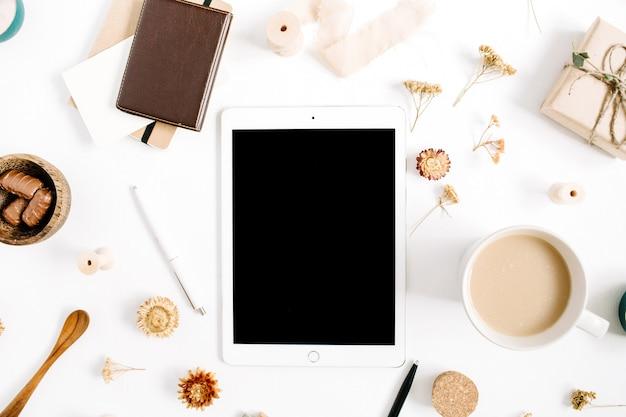 Espace de travail de blogueur ou de pigiste avec tablette, tasse à café, ordinateur portable, bonbons et accessoires sur fond blanc. mise à plat, vue de dessus bureau à domicile de style marron minimaliste. concept de blog de beauté.