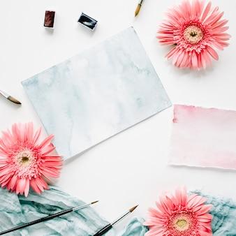 Espace de travail. bourgeons de gerbera rose et papier aquarelle avec pinceau et textile bleu sur blanc