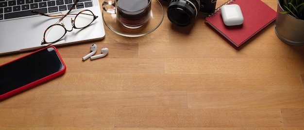 Espace de travail branché avec ordinateur portable, smartphone, fournitures et espace copie sur table en bois