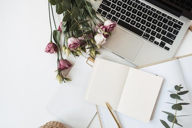 Espace de travail de bureau avec cahier de feuille de papier vierge, ordinateur portable, bouquet de fleurs de roses, branche d'eucalyptus sur tableau blanc