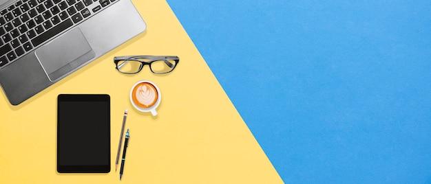 Espace de travail de bureau coloré avec ordinateur portable, lunettes, tablette, café avec espace de copie