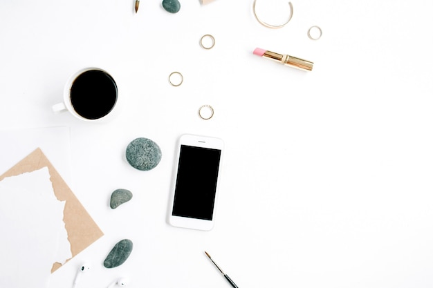Espace de travail de bureau à domicile avec café, téléphone portable, enveloppe artisanale, pierres, écouteurs et papier vierge sur une surface blanche
