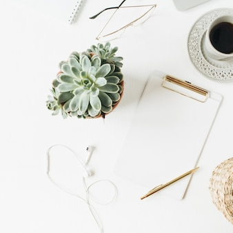 Espace de travail de bureau à domicile avec espace copie vierge maquette presse-papiers, écouteurs, lunettes, succulentes sur blanc