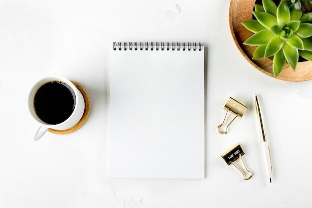 Espace de travail de bureau à domicile de mode plat avec succulentes, tasse de café, carnet de papier vierge, stylo et clips. vue de dessus. copier l'espace.