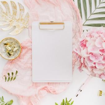 Espace de travail de bureau à domicile moderne avec presse-papiers vierge, fleurs d'hortensia rose et accessoires sur surface blanche