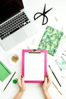 Espace de travail de bureau à domicile avec ordinateur portable, ordinateur portable et papeterie. mains de femme tenant le presse-papiers. concept de blog plat lapointe, vue de dessus.
