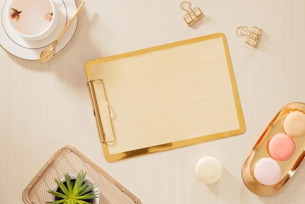 Espace de travail de bureau à domicile pour femmes avec presse-papiers, macarons, stylo, tasse à café sur fond pastel. concept de mode de vie plat lapointe, vue de dessus.