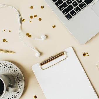 Espace de travail de bureau à domicile avec presse-papiers, ordinateur portable, café sur beige