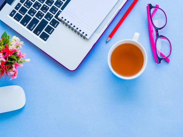 Espace de travail de bureau féminin avec des accessoires de bureau sur fond bleu.