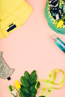 Espace de travail de bureau féminin avec des cosmétiques, des vêtements de printemps légers, des accessoires et des fleurs de tulipe sur fond jaune. concept de printemps.