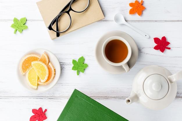 Espace de travail de bureau féminin à plat avec agenda, lunettes, livre, tasse à thé, bonbons et décoration en feutre.