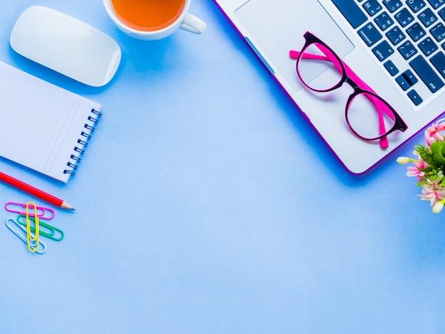 Espace de travail de bureau féminin vue de dessus avec des accessoires de bureau sur fond bleu.