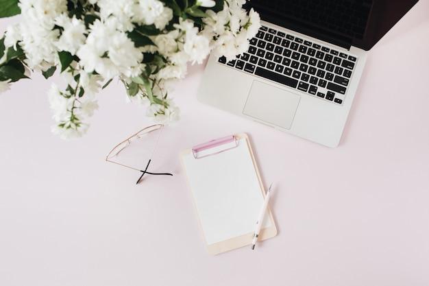 Espace de travail de bureau avec ordinateur portable, bouquet de fleurs et presse-papiers de maquette espace copie papier vierge sur table rose
