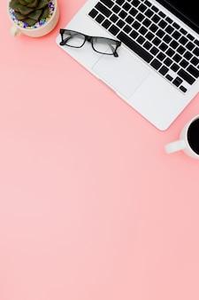 Espace de travail de bureau plat laïque avec ordinateur portable vierge, presse-papiers, fond d'ordinateur portable vue de dessus et espace de copie sur fond rose