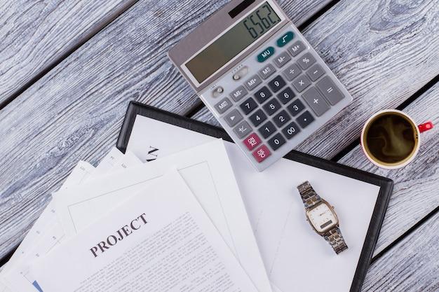 Espace de travail de bureau avec projet de plan d'affaires et calculatrice. papiers et tasse de café sur bois blanc. vue de dessus à plat.