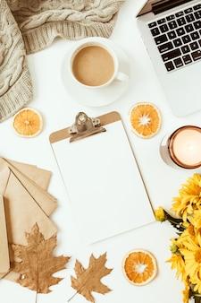 Espace de travail de bureau de table de bureau à domicile avec presse-papiers décoré de bouquet de fleurs de marguerite jaune, tasse à café, tranches d'orange, plaid. mise à plat, vue de dessus