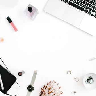 Espace de travail de cadre de blogueur ou d'indépendant avec le cahier de fleur de protea d'ordinateur portable et les accessoires féminins sur le fond blanc