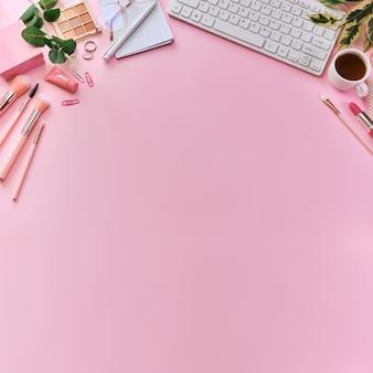Espace de travail avec clavier blanc, bloc-notes, lunettes, stylos, accessoires de beauté, clavier, fournitures de bureau, feuille verte et tasse à café sur une surface rose