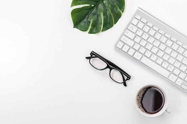 Espace de travail avec clavier d'ordinateur, fournitures de bureau, feuille verte et tasse à café sur fond blanc.
