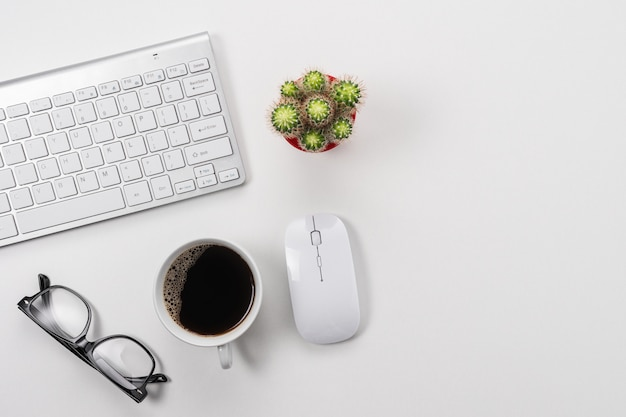 Espace de travail avec clavier d'ordinateur, fournitures de bureau et tasse à café sur fond blanc.