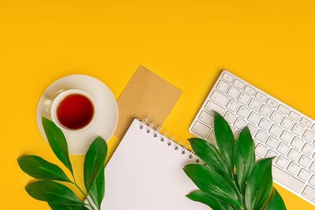 Espace de travail avec clavier, tasse de thé avec des feuilles vertes sur fond jaune