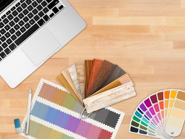 Espace de travail de concepteur vue de dessus avec ordinateur portable et guide des couleurs