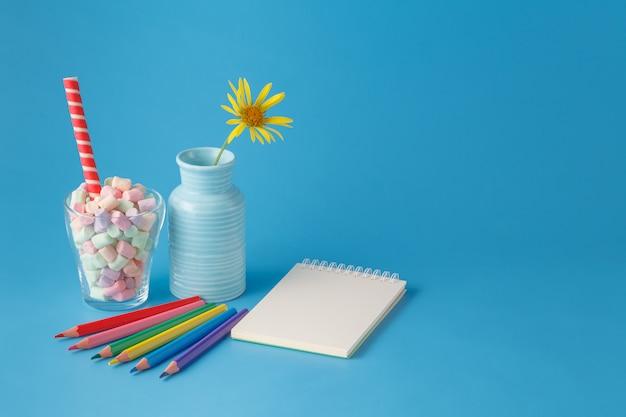 Espace de travail avec des crayons de couleur et un cahier