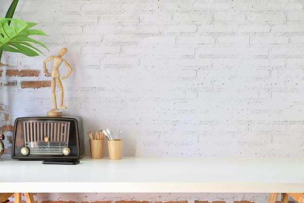 Espace de travail dans le loft avec radio vintage, fournitures de concepteur et espace de copie