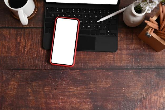 Espace de travail design avec tablette informatique, téléphone intelligent, tasse à café et porte-crayon sur un bureau en bois.