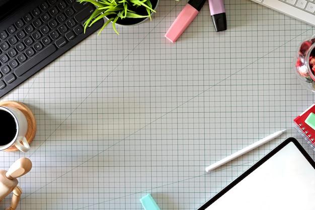 Espace de travail du graphiste avec une tablette à crayon, un ordinateur, des échantillons de couleur et un espace de copie