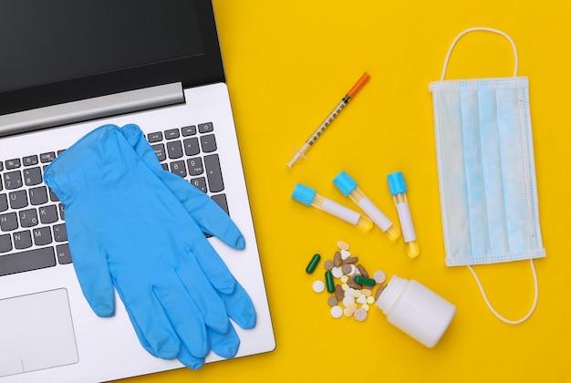 Espace de travail du médecin avec ordinateur portable sur fond jaune. vue de dessus. mise à plat